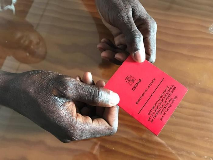 """Oumar,"" a 24-year-old from Mali, holds his asylum seeker card. Oumar had no opportunity to apply for asylum upon disembarkation in Algeciras, and was only able to do so when remanded to the Tarifa immigration detention center. He was released ten days la"