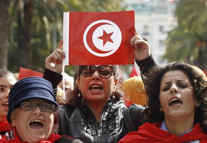 A Tunisian woman holds up a flag during a march to celebrate International Women's Day in Tunis March 8, 2014. © 2014 Reuters