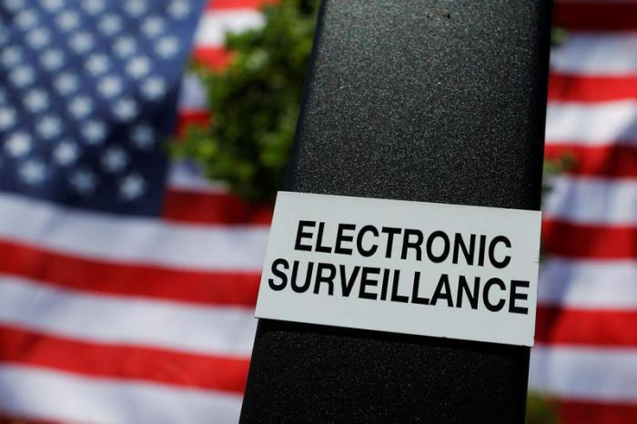 A notice of electronic surveillance is posted near a 95-by-50-foot American flag unfurled on the side of an apartment complex in Manchester, New Hampshire, U.S., June 14, 2017.
