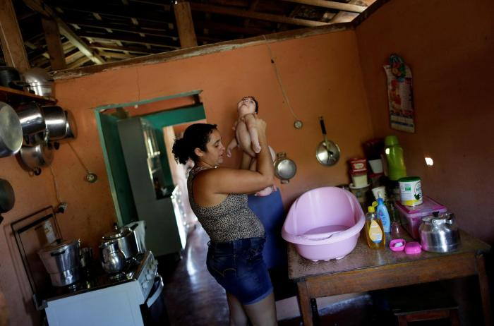 Raquel bathes her daughter Heloisa, a girl with Zika syndrome born in April 2016. Raquel says she cannot afford the medicines her twin daughters need for convulsions.