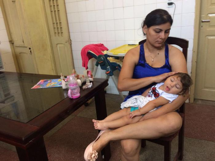 Jusikelly, 32, holds her daughter, a girl with Zika syndrome born in November 2015, in their home in Pernambuco state.