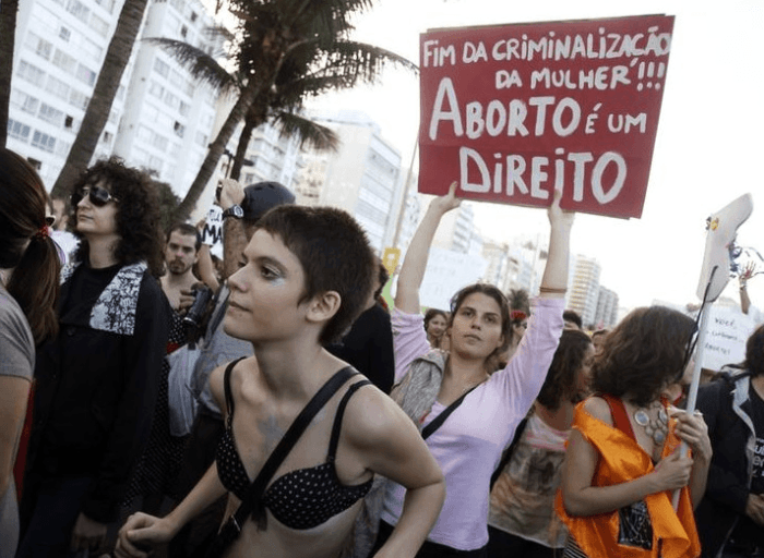 "People participate in the SlutWalk protest on Copacabana Beach, here pope Francis will celebrate mass at night, in Rio de Janeiro, July, 2013. The sign reads ""No more criminalization of women, abortion is a right"". ©  REUTERS/Pilar Olivares"