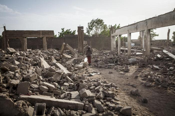 A girl walks through the rubble of destroyed buildings in Banki, northeast Nigeria, April 2017.