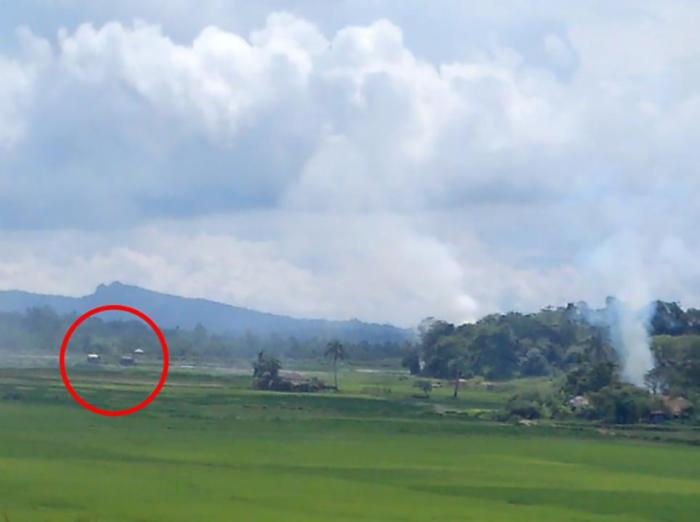 A screen grab of a video shows two dark-colored Burmese military trucks within several hundred meters of a burning village.