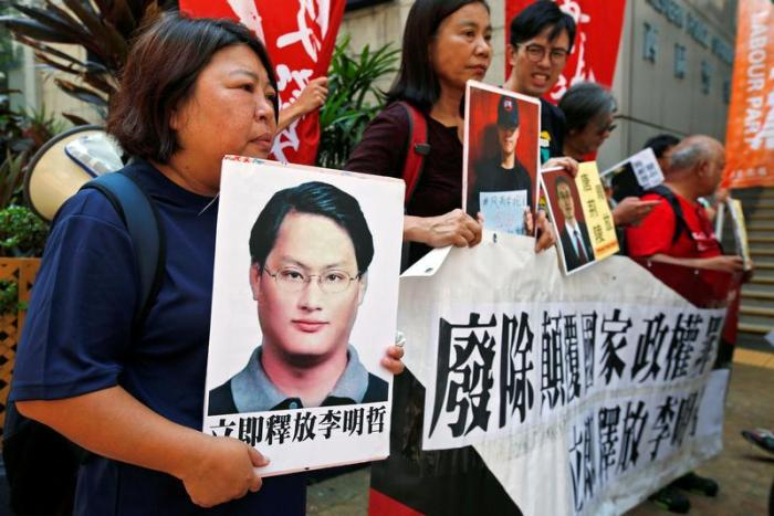 Pro-democracy protesters carry a photo of detained Taiwanese rights activist Lee Ming-Che (L) and other activists during a demonstration in Hong Kong, China September 11, 2017.