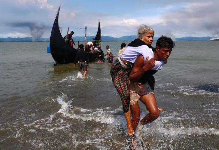 Smoke is seen on Myanmar's side of border as an old Rohingya refugee woman is carried after crossing the Bangladesh-Myanmar border by boat through the Bay of Bengal in Shah Porir Dwip, Bangladesh, September 15, 2017.