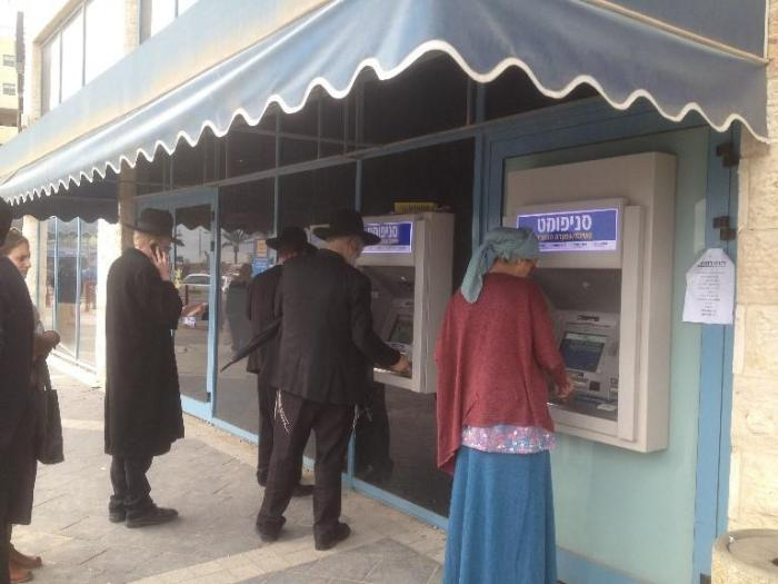 Customers use ATMs outside a bank branch in the Israeli settlement of Modi'in Ilit.