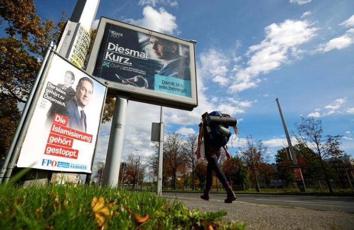 A woman walks past election campaign poster of far right Freedom Party (FPOe) head and top candidate Heinz-Christian Strache and People's Party (OeVP) top candidate and Foreign Minister Sebastian Kurz in Vienna, Austria October 4, 2017.