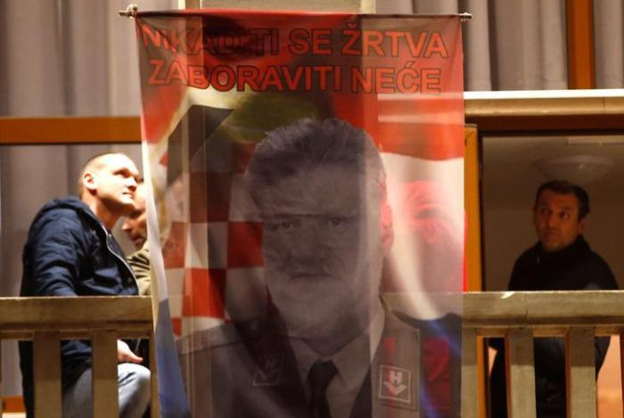 "Bosnian Croats in Mostar, Bosnia and Herzegovina hang a flag displaying a portrait of General Slobodan Praljak and a message that reads ""Your sacrifice will never be forgotten"", as people pray and light candles for the convicted general."
