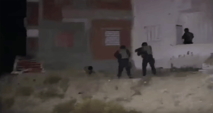 Military experts said this still from the Interior Ministry video appeared to show that the commandos had secured the area before shooting the man. A third commando can be seen entering a room through an exterior door. Experts said that a commando taking