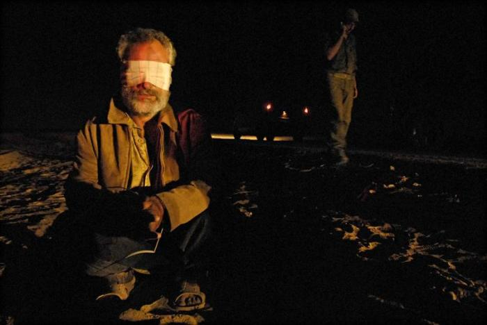 A blindfolded Palestinian, detained during an Israeli military operation in Gaza, sits on the ground at a crossing between Israel and the Gaza Strip on November 7, 2007.