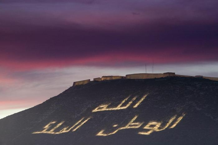 "Morocco's motto ""God, Nation, King"" -- here illuminating a hillside in Agadir -- is the basis for red lines restricting speech in the kingdom"