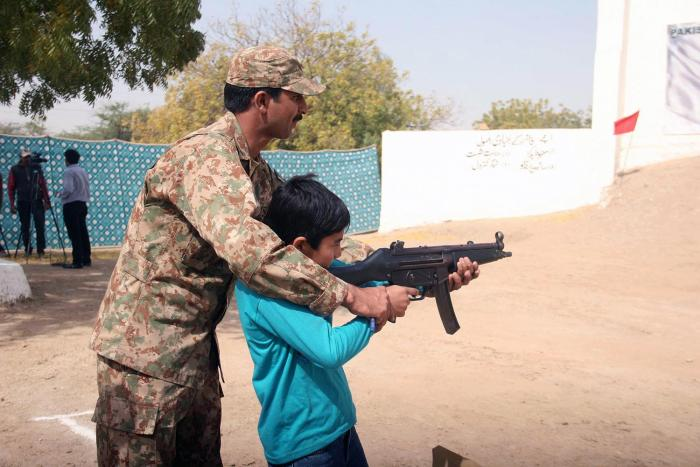 A Pakistani soldier assists a child aim a military assault rifle during a security training in Karachi, Pakistan, February  2016.