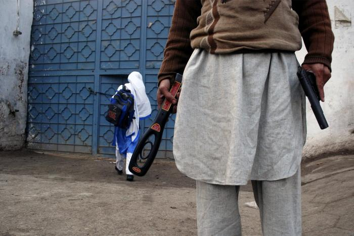 A guard with a gun and a metal detector stands outside a school after it reopened in Peshawar, January 2015.