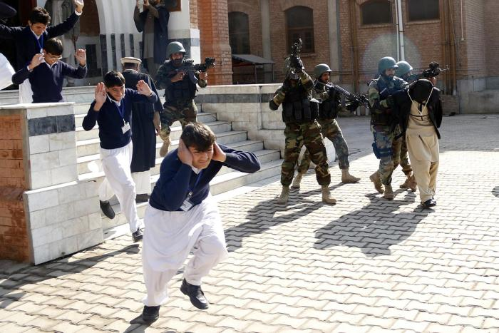 School children flee as soldiers conducting an exercise to repel militant attacks detain a mock-militant (R) at the Islamia Collegiate School in Peshawar, Pakistan, February 2016.