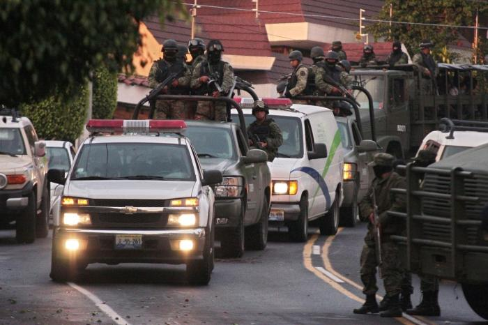 A military convoy protects the vehicle of the Forensic Service which allegedly carries the remains of Ignacio 'Nacho' Coronel in Guadalajara on July 30, 2010.