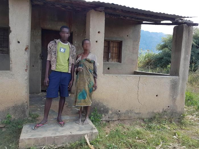 A woman and her son in front of their house with bullet holes in Mukodza village, Gorongosa. They said soldiers arrived in army vehicles and fired without warning at the house in June 2016, forcing them to flee through a window.