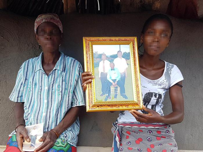 The wife and daughter of the regulo (traditional chief) of Muxungue, Makotori José Mafussi, show a photo of Mafussi (seated) and two relatives. Apparent Renamo fighters killed Mafussi at his home on July 21, 2016.