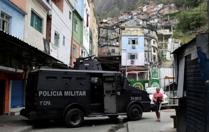 "Police officers patrol the Rocinha slum after violent clashes between drug gangs, in Rio de Janeiro, Brazil September 29, 2017. The banner reads: ""The Rocinha asks for peace."""