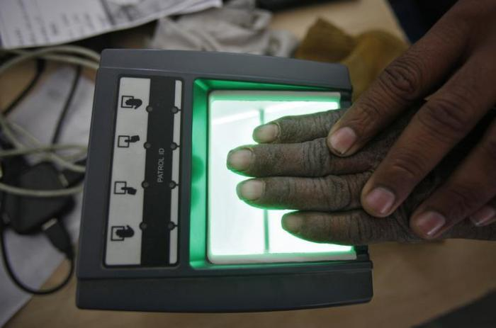 201801asia_india_dna A villager goes through the process of a fingerprint scanner for the Unique Identification (UID) database system at an enrolment center at Merta district in the desert Indian state of Rajasthan on February 22, 2013.