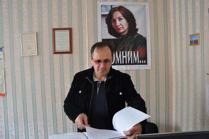 Oyub Titiev stands in front of a portrait of his murdered colleague, Natalia Estemirova, in Memorial's Grozny office, Grozny, Chechnya, Russia.