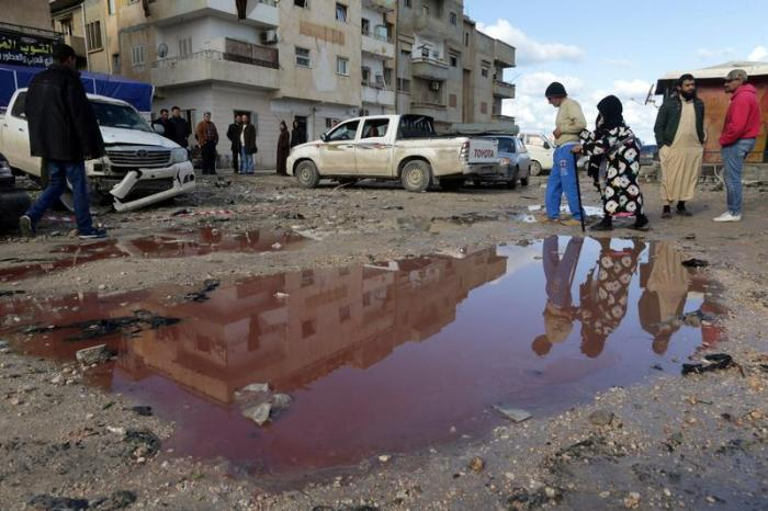 People walk near a puddle of water mixed with blood at the site of twin car bombs near a mosque in the Salmani neighborhood of Benghazi that resulted in scores of deaths and injuries, Libya, January 24, 2018. © 2018 Reuters
