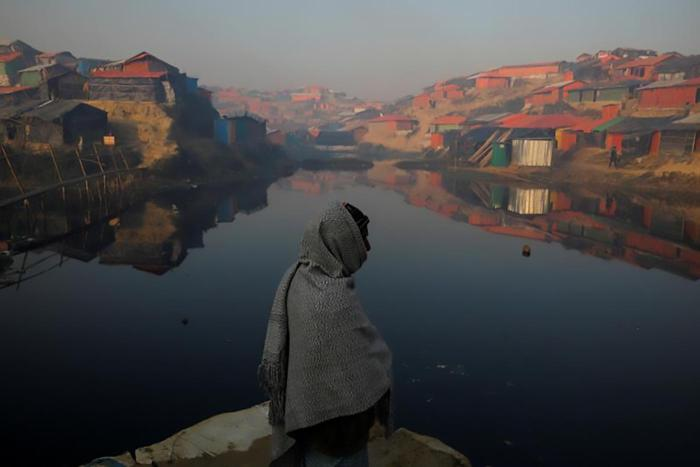 A Rohingya refugee stands next to a pond in the early morning at the Balukhali refugee camp near Cox's Bazar, Bangladesh December 26, 2017. REUTERS/Marko Djurica TPX IMAGES OF THE DAY