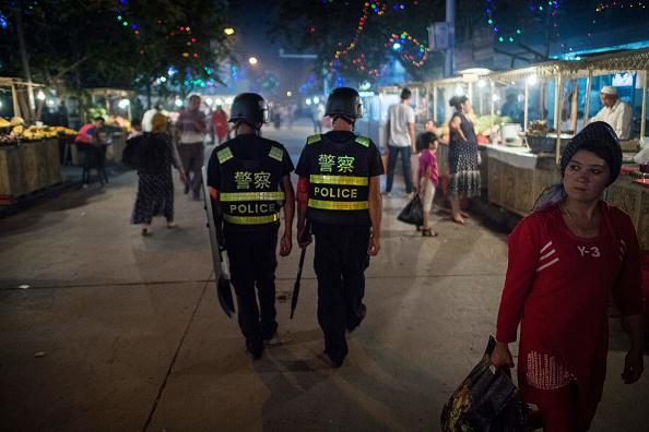 Chinese police patrol a night market near Id Kah Mosque in Xinjiang, a day before the Eid al-Fitr holiday, June 25, 2017.