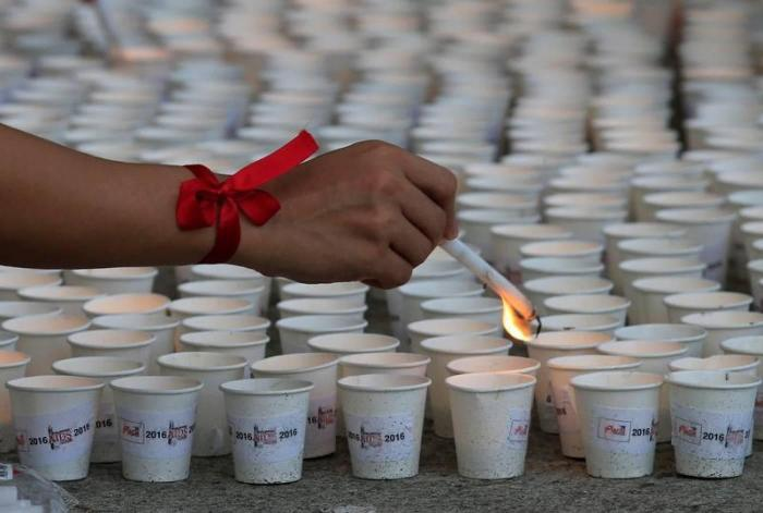 A supporter lights candles in commemoration of HIV/AIDS victims in the Philippines at a ceremony in Quezon City, Metro Manila, May 14, 2016.