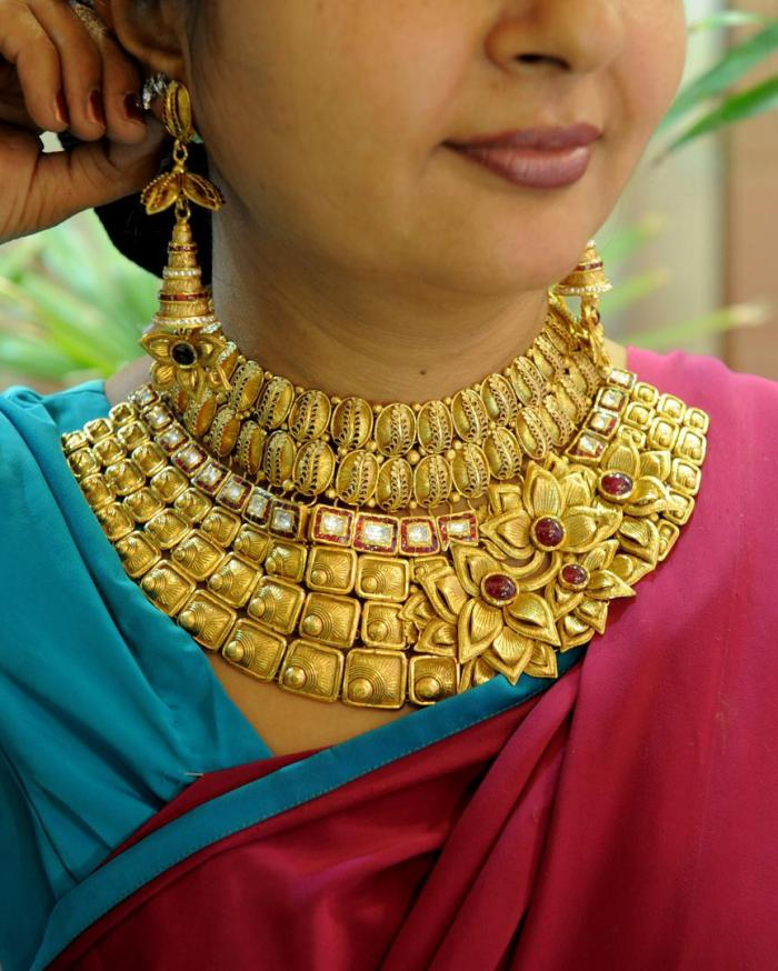 A woman tries on a necklace at the Tribhovandas Bhimji Zaveri (TBZ) showroom in Ahmedabad, India, August 2010.