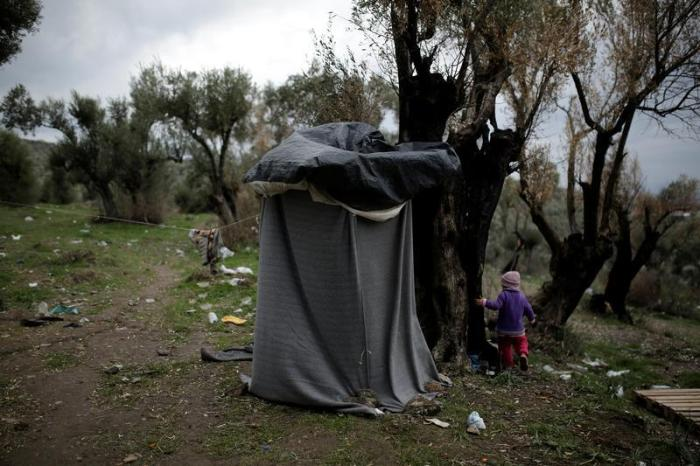 A girl walks next to a self-made shower at a makeshift camp for refugees and migrants next to the Moria camp on the island of Lesbos, Greece, November 30, 2017.