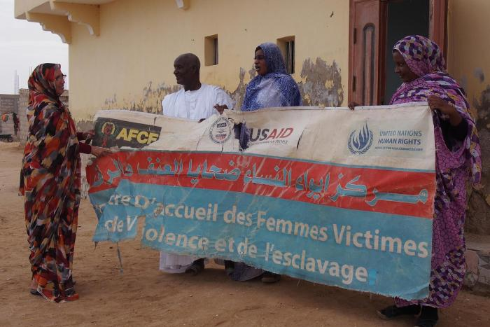 "Aminetou Ely and staff of the center of the Association of Women Heads of Family in Dar Naim, with a banner for ""The Reception Center for Women Victims of Violence and Slavery."""