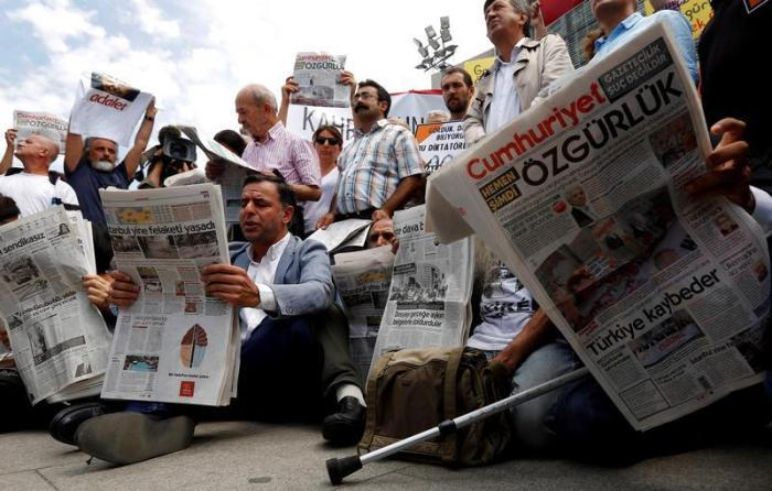 Press freedom activists read opposition newspaper Cumhuriyet during a demonstration in solidarity with the jailed members of the newspaper outside a courthouse, in Istanbul, Turkey, July 28, 2017.