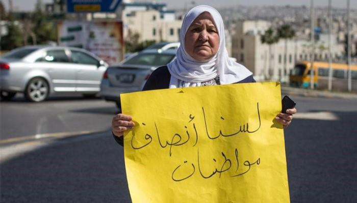 "The late Nima Habashneh, a leading activist in the movement for equal citizenship rights in Jordan, holds a sign that reads, ""we are not half citizens"", during a protest in front of the Prime Ministry in Amman, Jordan on March 22, 2014."