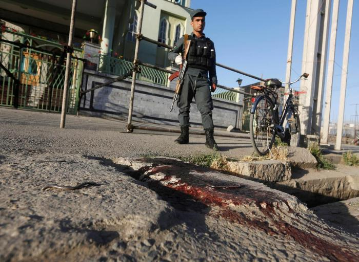 A policeman stands on a bloodstained street following the suicide attack at the Al-Zahra Mosque in Kabul, June 16, 2017.