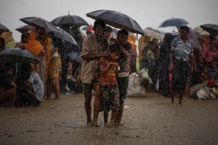 Rohingya refugees try to take shelter from torrential rain as they are held by the Border Guard Bangladesh (BGB) after illegally crossing the border, in Teknaf, Bangladesh, August 31, 2017.