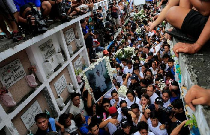 Mourners watch as Kian delos Santos, a 17-year-old student who was shot during anti-drug operations is buried in Caloocan, Metro Manila, Philippines August 26, 2017.