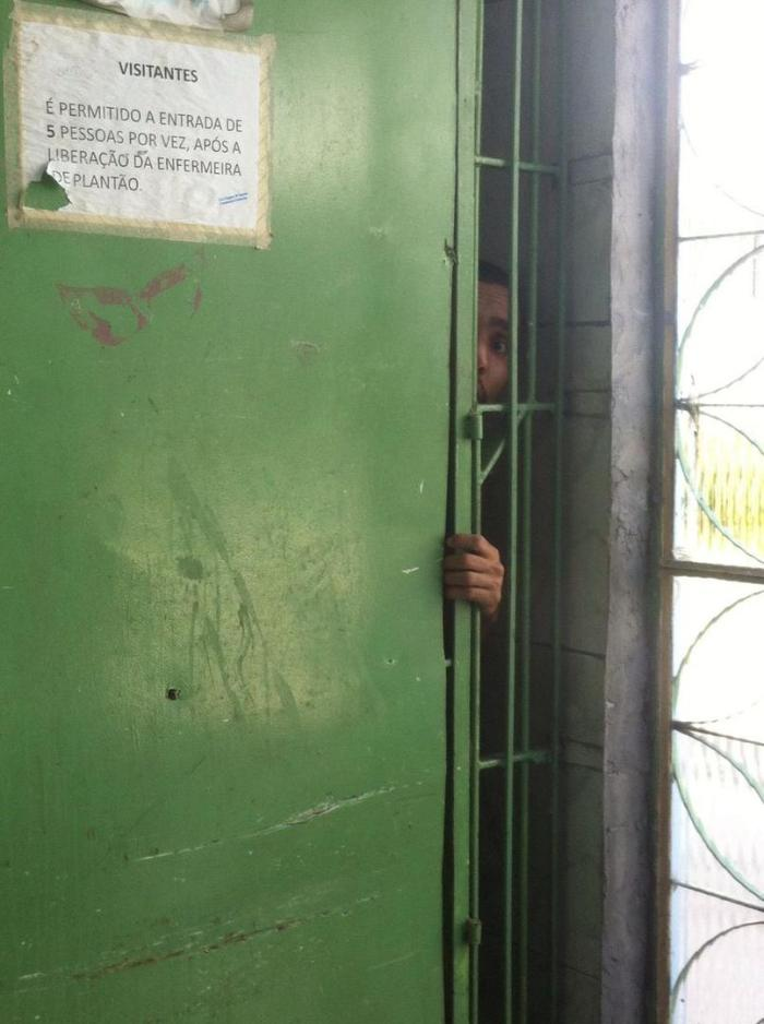 A man with disabilities looks out through the bars of a psychiatric ward in an institution in Rio de Janeiro. Persons locked in this section of the institution never left their rooms, according to staff.