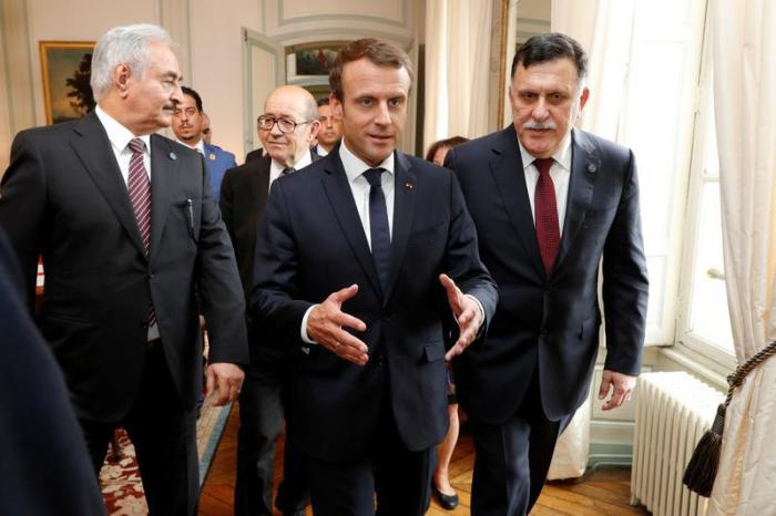 French President Emmanuel Macron walks with Libyan Prime Minister Fayez al-Sarraj and General Khalifa Haftar, commander in the Libyan National Army (LNA), before a meeting for talks over a political deal to help end Libya's crisis in La Celle-Saint-Cloud