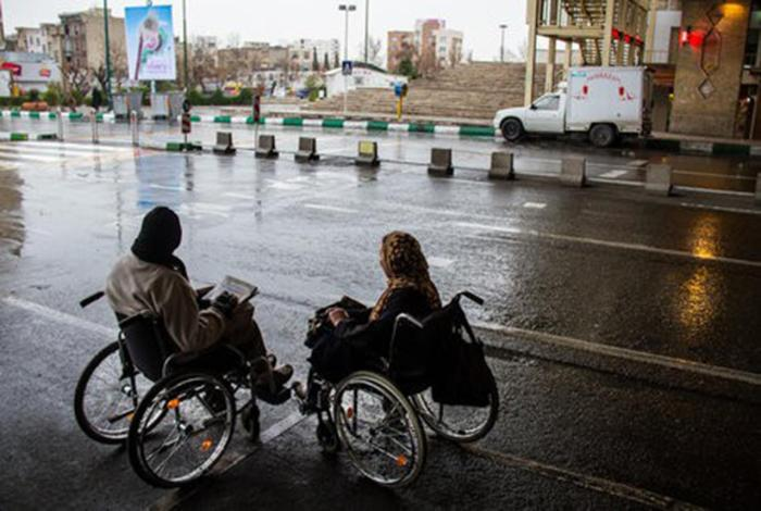 Two women who use wheelchairs attempting to cross a road in Tehran, the capital of Iran.