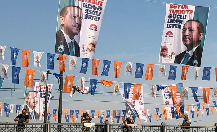 "President Recep Tayyip Erdogan's campaign posters read ""Great Turkey wants a strong leader"", flying above election banners for the ruling Justice and Development Party (AKP) he chairs, Galata Bridge, Istanbul, June 2018."