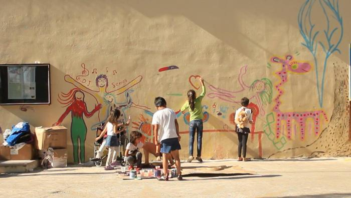 Children decorate a wall at PIKPA