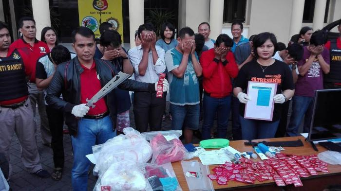 Authorities show condoms, lubricant, and HIV test results to the media while detainees cover their faces after police raided a hotel room in Surabaya.