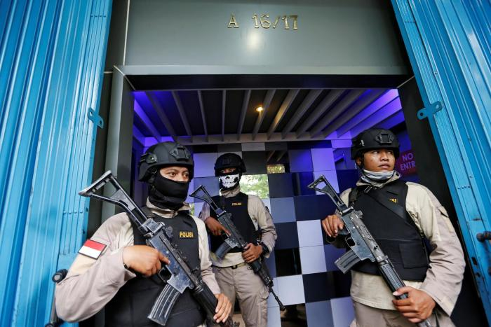 Police officers guard the entry of the T1 night club in Jakarta on October 9, 2017, after they raided it and arrested 10 people for alleged violations of the anti-pornography law.