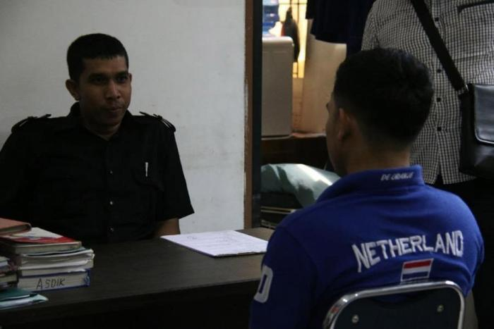 On March 29, 2018, vigilantes forcibly entered a private house in Aceh province and called the Sharia (Islamic law) police, who arrested two male college students for allegedly having sex. A police officer questions one of the men in the Sharia