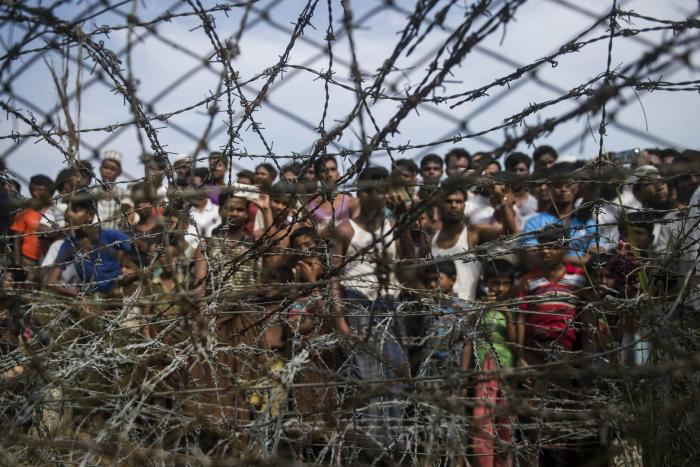 """Rohingya refugees gather behind a barbed-wire fence in the """"no-man's land"""" border zone between Myanmar and Bangladesh, April 25, 2018."""