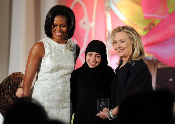 Former US First Lady Michelle Obama and former Secretary of State Hillary Clinton pose with Samar Badawi of Saudi Arabia as she receives the 2012 International Women of Courage Award during a ceremony at the US State Department in Washington, DC, on March