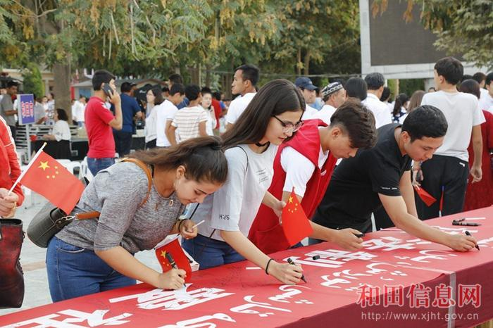 "Students sign their names on a banner that reads, among other slogans, ""Love the Motherland"" in Hotan, Xinjiang."