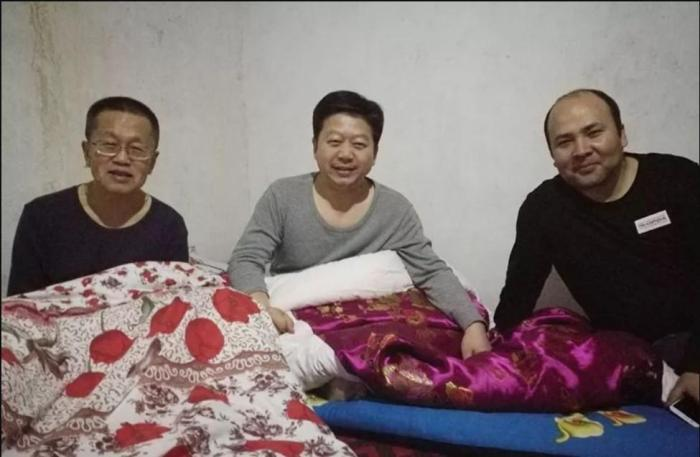 "A state press photo showing Chinese officials sharing sleeping quarters with Turkic Muslim families during compulsory homestay ""Becoming Family"" program in Xinjiang."