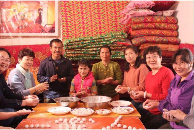"A State press photo showing Chinese officials staying with Turkic Muslim families during compulsory homestay ""Becoming Family"" program in Xinjiang."